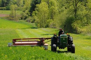 Farmer cutting grass in Shelburne, Vermont.